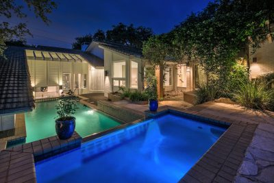 Backyard swimming pool lit up at night of an Austin-area home